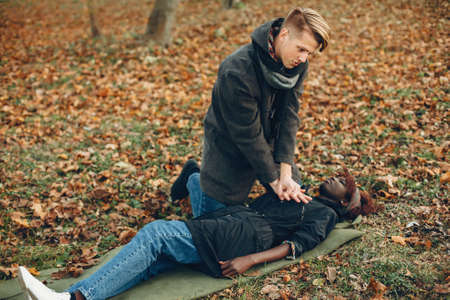 Man in a autumn park help african girl