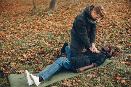 Man in a autumn park help african girl