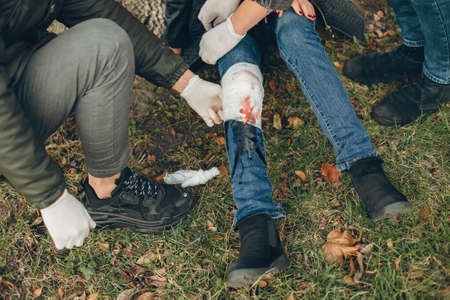 Two boys help a woman with a leg injury Reklamní fotografie