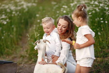 Mother with two children feeds goat in the park.