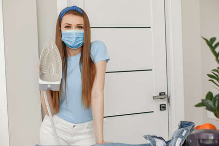 Woman in a blue t-shirt ironing laundry at home