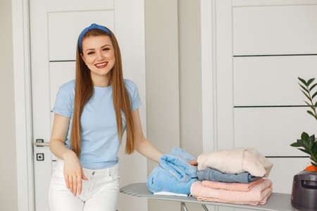 Woman in a blue t-shirt done doing laundry at home
