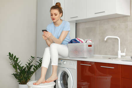 Woman sitting on a washing machine while waiting for laundry