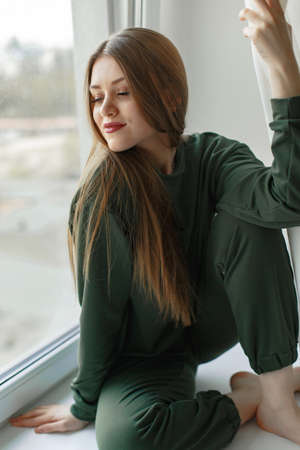 Woman sitting on a windowsill at home