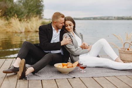 People sitting by the water with picnic set Standard-Bild - 158270512
