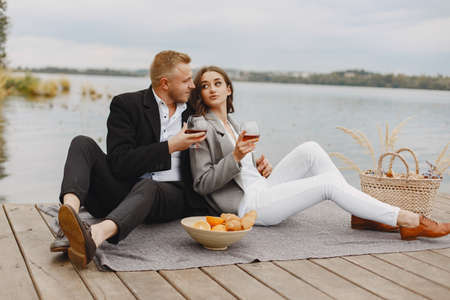 People sitting by the water with picnic set Standard-Bild - 158270513
