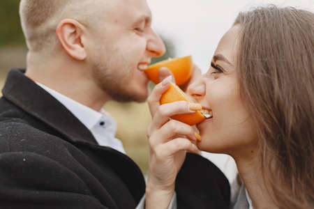 Beautiful couple spend time together eating orange