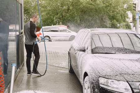Man in a black sweater. Male washing a car. Guy spray a water. 版權商用圖片