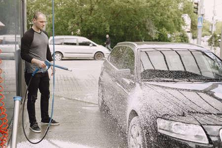 Handsomen man in a black sweater washing his car Standard-Bild - 158270918
