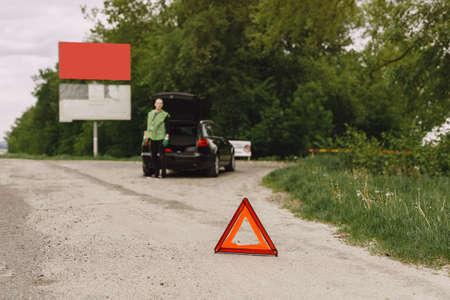 Driver putting warning triangle on asphalt road. Emergency stop concept. Standard-Bild - 158271168