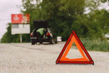 Driver putting warning triangle on asphalt road. Emergency stop concept.