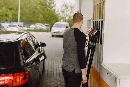 Man on a gas station. Guy refuelong a car. 版權商用圖片