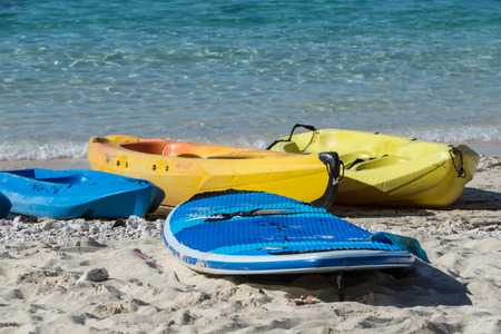 Kayaks, Paddle boards, surfboards, water gear and beach toys in the sand with blue water.  Activities and fun await!