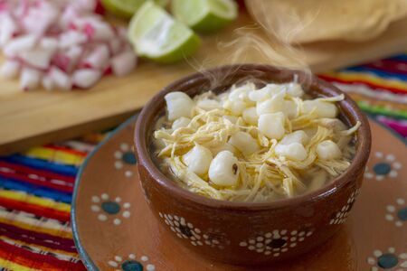 Pozole de comida tradicional mexicana con rábanos, limones y tostadas, chile y orégano con un colorido fondo mexicano. Esta comida es tradicional en el país de México Foto de archivo