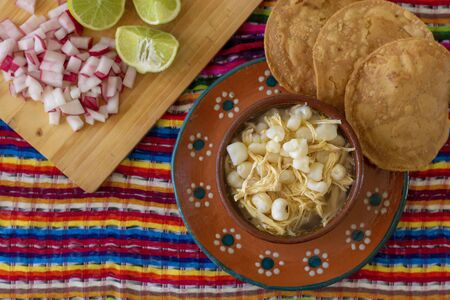 Traditional mexican food pozole accompanied by radishes, lemons and toast, chile de arbol and oregano with a colorful Mexican background. This food is traditional in the country of Mexico