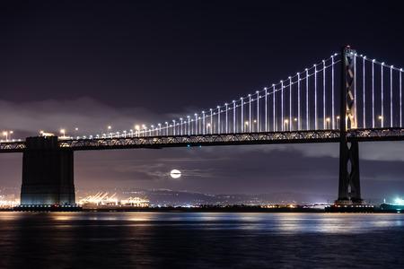 San Francisco-Oakland Bay Bridge at night with the moon