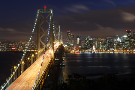 San Francisco Bay Bridge and skyline at night with city lights