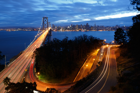 san francisco bay bridge: San Francisco Bay Bridge and skyline at night with city lights
