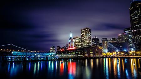 Ferry Building y el puente de la bahía iluminada por la noche en San Francisco California EE.UU. Foto de archivo - 41249616