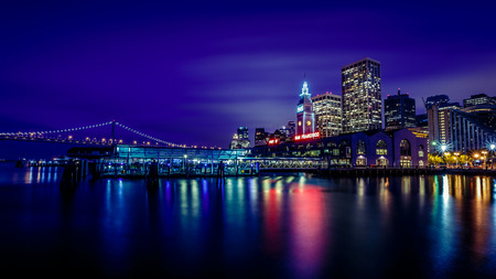 Ferry Building and Bay Bridge illuminated at night in San Francisco California USA Stock Photo