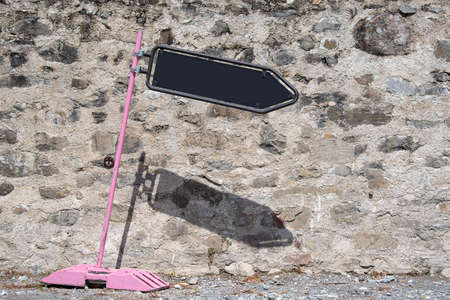Tilted pink road sign with black board arrow showing direction. Wall background in sunny day. Signpost and indication.