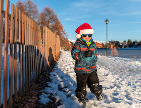 Boy with Santa red hat against a winter landscape background. Happy smiling child in the snow at Christmas standing beside tall plants outdoors. Crans Montana in Switzerland. Stock Photo