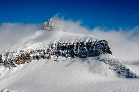 Winter landscape of snowcapped mountains with blue sky and clouds on sunny day. Famous Diablerets Glacier in Switzerland. Tranquility and beauty in nature.