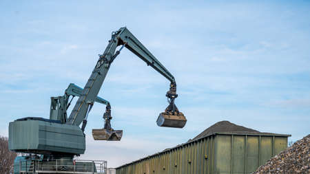Big excavator working by handling pebbles from the pile of stones to container. Working machine in construction site. Industry.