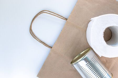 Food supplies on paper bag during quarantine and self-isolation. Donation. Canned food, toilet paper, top view.
