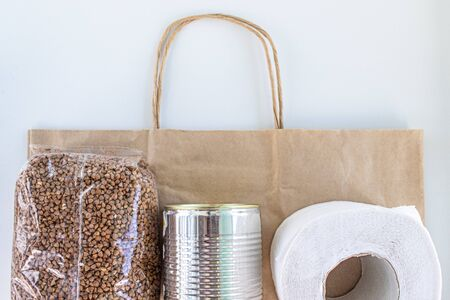 Food supplies on paper bag during quarantine and self-isolation. Donation. Buckwheat, canned food, toilet paper, top view. Foto de archivo