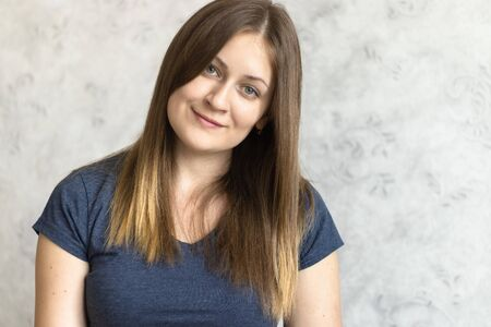 Portrait of beautiful young smiling girl. Close up of usual woman with cute smile. Brown hair or a fair Russian pretty girl wearing casual dark blue t-shirt.