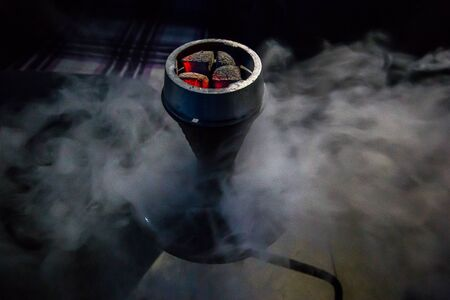 Coals for hookah close-up. Burning coals on the hookah bowl in the smoke. Concept of vacation with friends. Foto de archivo