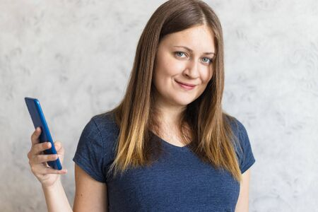 Portrait of young girl holding a mobile phone. Woman is going or wants to call her parents, relatives, friends. Beautiful girl with long brown hair and a regular dark blue t-shirt. Foto de archivo
