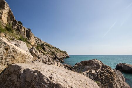 Travel in Crimea, Russia. Nature background. Colorful landscape with blue sea, mountains, rocks and sunlight in clear warm summer cloudless day. Concept of vacation on the coast.