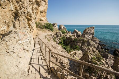 Travel in Crimea, Russia. Nature background. Colorful landscape with blue sea, mountains, rocks and sunlight in summer cloudless day. Concept of vacation on the coast. Golitsyn trail, mountain trail.