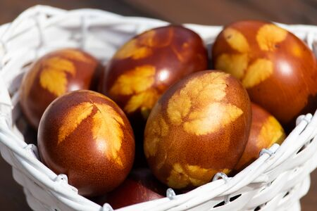 Easter eggs colored with onion husks in a white wicker basket in shape of heart. The old traditional way of nandmade decoration.