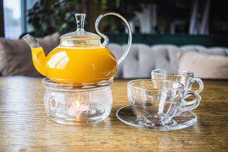 Herbal sea buckthorn tea in a transparent teapot and in a transparent glass with double heating bottom in restaurant. Concept of warmth and comfort. Mango and passion fruit tea.