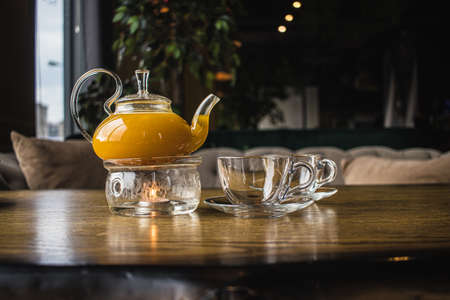 Herbal sea buckthorn tea in a transparent teapot and in a transparent glass with double heating bottom in restaurant. Concept of warmth and comfort. Mango and passion fruit tea