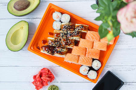 Roll made of Fresh Raw Salmon, Smoked Eel, Cream Cheese and Avocado inside. Topped with Smoked Eel or unagi top view. Flatlay of food