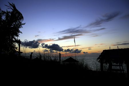 Tropical sunset viewed from land with beach straw hut to the side. Stock Photo - 3076421