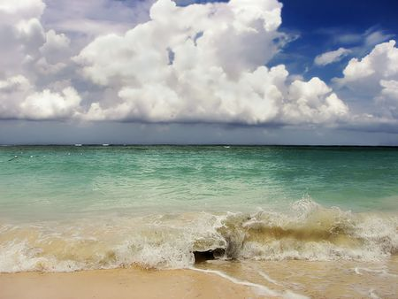 Wave mid way through breaking on tropical beach with tall cumulus nimbus clouds on the horizon. Stock Photo - 3076418