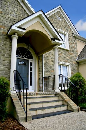 Entrance door to a modern stone house. Archivio Fotografico