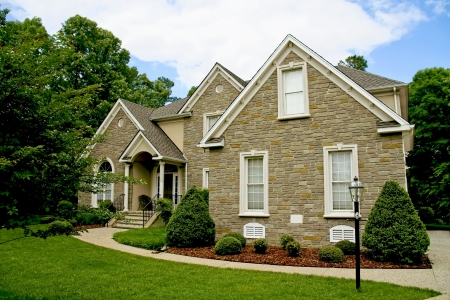 suburban: Modern stone house with well kept yard.