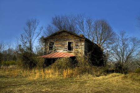 Old abandoned and rundown house sitting in the middle of a field. photo