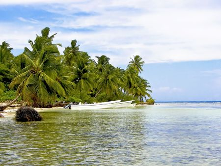 Tropical cove surrounded with palm trees.  Beautiful clear water with boats parked by shoreline.