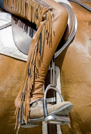 Close up of custom horse back riding chaps with fringe.