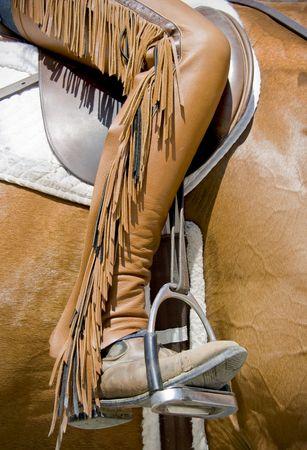 western saddle: Close up of custom horse back riding chaps with fringe.