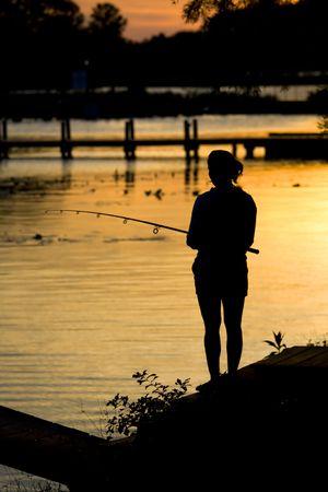Women fishing on shoreline at dusk during a sunrise.