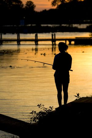 Women fishing on shoreline at dusk during a sunrise.