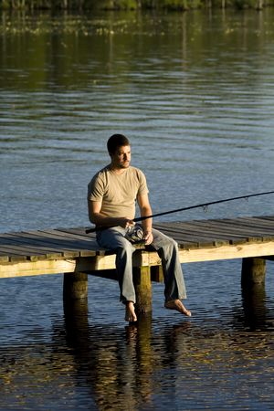 Man sitting alone on a pier fishing in a bay. Stock Photo - 3119899